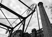历史的运河铁锁式桥梁的单色图象在有大老磨房大厦的哈德斯菲尔德西约克郡与一块高石头 免版税库存图片