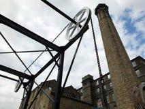历史的运河铁锁式桥梁的看法在有大老磨房大厦的哈德斯菲尔德西约克郡与一个高石烟囱 库存照片