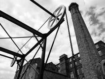 历史的运河铁锁式桥梁的看法在有大老磨房大厦的哈德斯菲尔德西约克郡 免版税库存照片