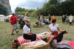 历史自行车-有历史的服装的人们会议野餐 免版税库存图片