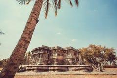 历史建筑学的例子在印度 棕榈树和12世纪Hoysaleshwara寺庙,印度 库存图片