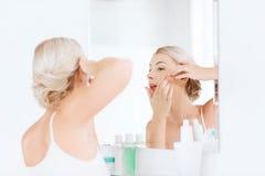 紧压丘疹的妇女在卫生间镜子 库存图片