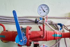压力表显示压力与一个蓝色门闩的在生产中色的红色 行业背景 免版税库存照片