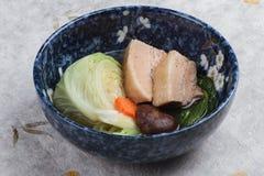 压力锅猪肚Kakuni用圆白菜,日本薤,椎茸,红萝卜在washi的蓝色陶瓷碗服务 库存照片