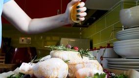 压在整个未加工的鸡的女性手新鲜的橙汁在烧烤平底锅用桔子蔓越桔和草本 免版税图库摄影