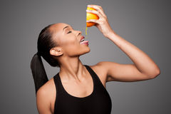 紧压橙汁果子的愉快的健康黑人亚裔妇女 库存图片