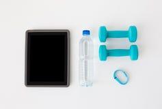 压片个人计算机、哑铃、健身跟踪仪和瓶 免版税图库摄影