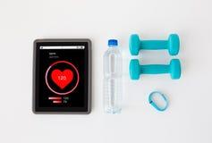 压片个人计算机、哑铃、健身跟踪仪和瓶 免版税库存照片