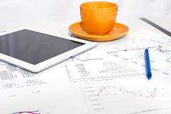 压片个人计算机、橙色杯子和纸与图表 库存照片