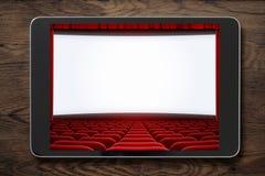 压片在木桌上的个人计算机与被显示的戏院屏幕 库存图片