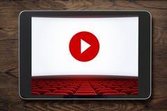 压片在木桌上的个人计算机与被显示的戏院屏幕 免版税库存照片
