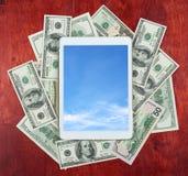压片在金钱美元和木头背景的中心,在屏幕上的云彩天空,企业概念和信息大模型安置的个人计算机 库存图片