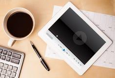 压片显示在屏幕上的个人计算机传媒播放装置有一杯咖啡的  库存图片