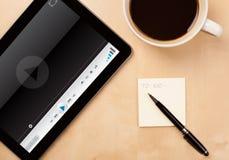 压片显示在屏幕上的个人计算机传媒播放装置有一杯咖啡的 免版税库存照片