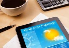 压片显示在屏幕上的个人计算机天气预报有一个杯子的coffe 免版税库存照片