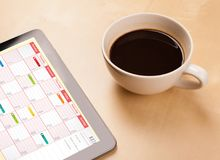 压片显示在屏幕上的个人计算机日历有一杯咖啡的在d的 免版税图库摄影