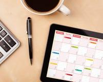 压片显示在屏幕上的个人计算机日历有一杯咖啡的在d的 免版税库存图片