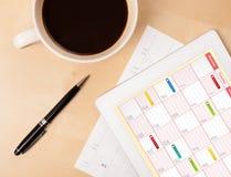 压片显示在屏幕上的个人计算机日历有一杯咖啡的在d的 图库摄影