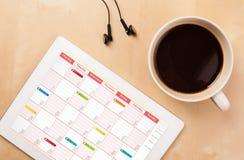 压片显示在屏幕上的个人计算机日历有一杯咖啡的在d的 免版税库存照片