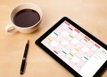 压片显示在屏幕上的个人计算机日历有一杯咖啡的在d的 库存图片