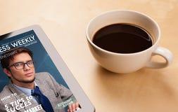 压片显示在屏幕上的个人计算机杂志有一杯咖啡的在d的 免版税库存照片
