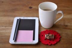 压片计算机、白色coffe杯子和巧克力块在木背景 库存图片