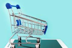 压片计算机和小推车购物的在深蓝背景 3d概念互联网回报购物 复制空间 免版税库存图片