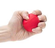紧压红色球的手 库存照片