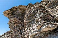 压缩的岩石分层堆积形成以各种各样的颜色和厚度,在中南部的海岸地中海islan 免版税库存图片