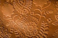 压花革接近的照片与一个花卉设计的在铁锈褐色 库存照片