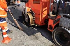 压路机和修理沥青的部分在车行道的建筑队在被操刀的路段 免版税库存照片