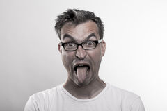 厌恶地拨开他的舌头的一个人的画象 免版税库存照片
