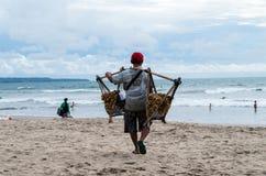 巴厘岛,印度尼西亚2017年1月:花生卖主沿库塔海滩走并且设法卖地方花生对游人 库存图片