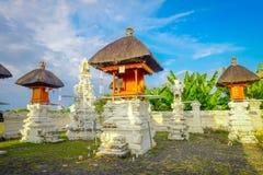 巴厘岛,印度尼西亚- 2017年3月11日:一个Indu寺庙的入口在Ubud,当一些秸杆小屋位于后院  库存照片
