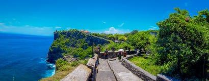 巴厘岛,印度尼西亚- 2017年3月11日:享受美好的晴天的未认出的人参观惊人的Uluwatu寺庙 免版税图库摄影