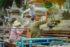 巴厘岛,印度尼西亚- 2017年4月05日:使用做的凿子的未认出的夫妇水泥艺术,在Ubud被找出的巴厘岛  免版税库存照片