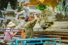 巴厘岛,印度尼西亚- 2017年4月05日:使用做的凿子的未认出的夫妇水泥艺术,在Ubud被找出的巴厘岛  库存照片
