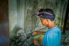 巴厘岛,印度尼西亚- 2017年3月08日:使用凿子的人做在水泥墙壁上的艺术,在登巴萨被找出的巴厘岛  免版税库存照片