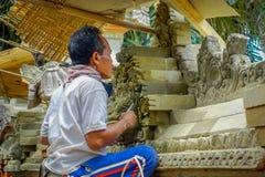巴厘岛,印度尼西亚- 2017年4月05日:使用凿子的人做水泥艺术,在Ubud位于印度尼西亚的巴厘岛 库存图片