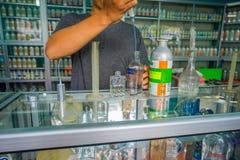 巴厘岛,印度尼西亚- 2017年3月08日:使用吸移管的人为了混合的精华能香水为permuse商店做准备  图库摄影
