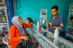 巴厘岛,印度尼西亚- 2017年3月08日:使用注射器和吸移管的未认出的人混合精华准备香水 库存照片