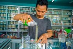 巴厘岛,印度尼西亚- 2017年3月08日:使用注射器和吸移管的未认出的人混合精华香水为做准备 图库摄影