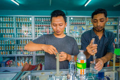 巴厘岛,印度尼西亚- 2017年3月08日:使用注射器和吸移管的未认出的人混合精华香水为做准备 免版税库存图片