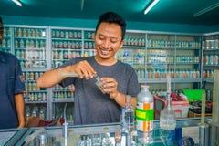 巴厘岛,印度尼西亚- 2017年3月08日:使用注射器和吸移管的未认出的人混合精华香水为做准备 免版税库存照片