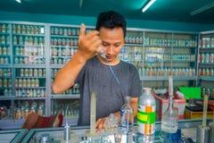 巴厘岛,印度尼西亚- 2017年3月08日:使用注射器和吸移管的未认出的人混合精华香水为做准备 库存图片