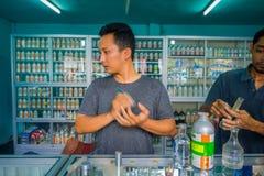 巴厘岛,印度尼西亚- 2017年3月08日:使用注射器和吸移管的未认出的人混合精华香水为做准备 库存照片