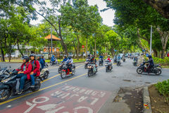 巴厘岛,印度尼西亚- 2017年3月08日:充分驾驶摩托车和汽车在路的未认出的人民交通 的treadled 库存照片