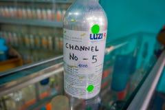 巴厘岛,印度尼西亚- 2017年3月08日:关闭有精华的一个金属瓶香水为香水商店做准备 免版税库存图片