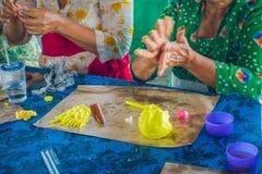 巴厘岛,印度尼西亚- 2017年3月08日:妇女印地安Sadhu面团为在Manmandir ghat的薄煎饼做准备在银行  免版税库存图片