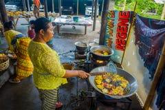巴厘岛,印度尼西亚- 2017年3月08日:妇女印地安Sadhu面团为在Manmandir ghat的薄煎饼做准备在银行  库存图片